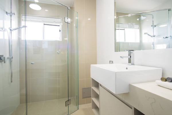 en suite bathroom with large adjustable shower, mirror and toilet in 1 bedroom executive apartment at Oaks Oasis Resort hotel in Caloundra, Sunshine Coast