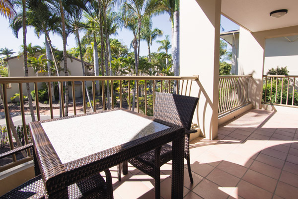 large private balcony in afternoon with table and chairs and views of Oaks Oasis Resort hotel in Caloundra, Sunshine Coast