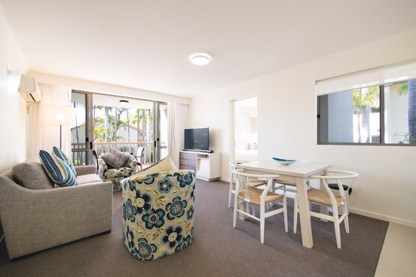 large living room area with air conditioning and television with Foxtel and private balcony outside