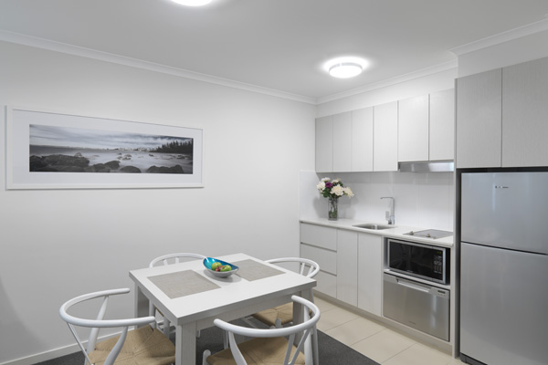 modern looking kitchen area with dining table and chairs and big refrigerator in air conditioned 2 bedroom dual key hotel apartment at Oaks Oasis Resort in Caloundra on Sunshine Coast, Queensland, Australia