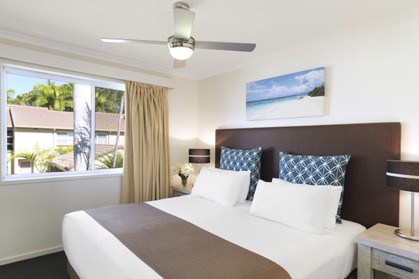 2 bedroom villa master bedroom with ceiling fan and clean bed sheets at Oaks Oasis Resort in Caloundra on Sunshine Coast, Queensland, Australia