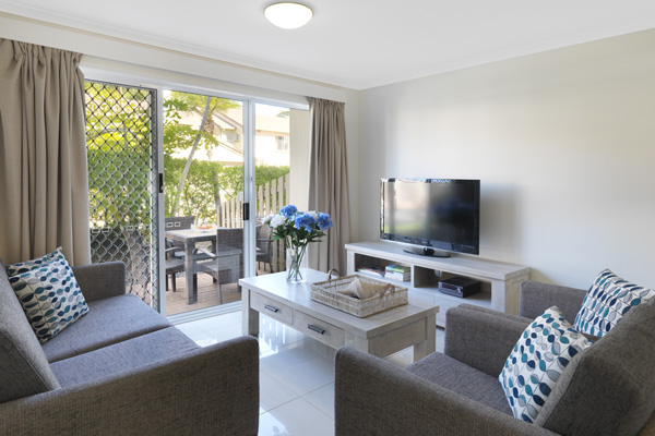 living room with television with Foxtel and Wi-Fi and private balcony with furniture in 3 bedroom villa at Oaks Oasis Resort in Caloundra on Sunshine Coast, Queensland, Australia