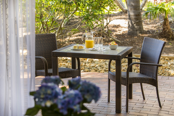 private courtyard balcony with orange juice glasses on table and chairs on either side in 2 bedroom villa
