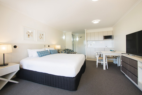 big bedroom with air conditioning, TV with Foxtel and en suite bathroom in Executive King hotel room apartment at Oaks Oasis Resort in Caloundra on Sunshine Coast QLD