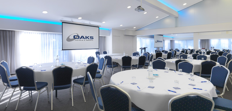 big conference venue ready for event with microphone, projector, tables and chairs at Oaks Oasis Resort in Caloundra on Sunshine Coast, Queensland, Australia