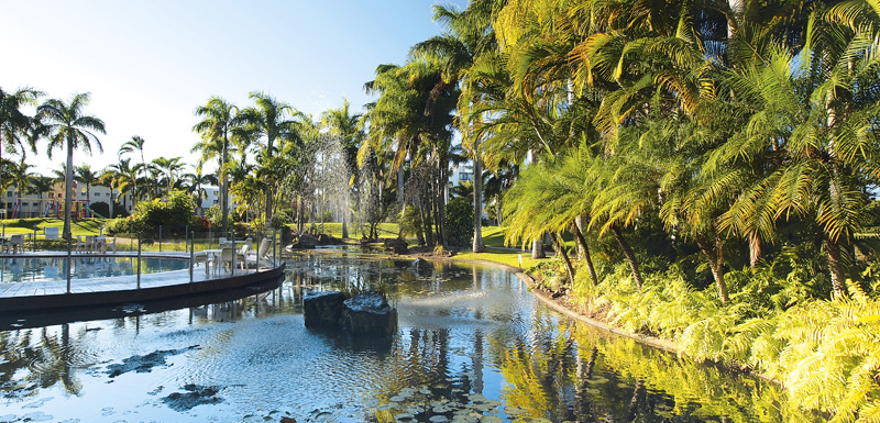 large fish pond with palm trees and water fountains at Oaks Oasis Resort hotel in Caloundra on Sunshine Coast, Queensland, Australia