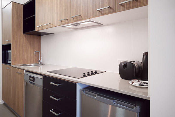 kitchen with microwave, fridge, toaster and kettle in one bedroom executive apartment at Oaks Rivermarque hotel in Mackay, Queensland, Australia