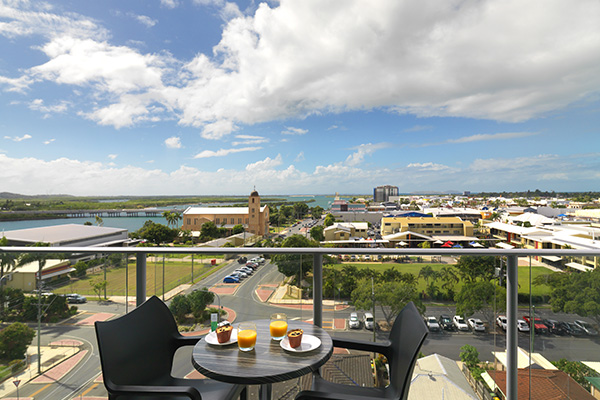 fresh fruit and breakfast on table on balcony of one bedroom apartment with views of Mackay at Oaks Rivermarque hotel