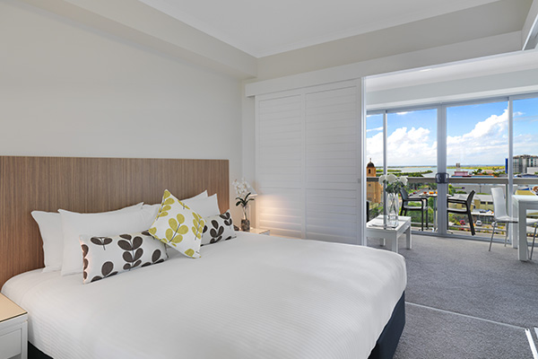 queen size bed in air conditioned one bedroom apartment with private balcony and Wi-Fi at Oaks Rivermarque hotel in Mackay, Queensland, Australia