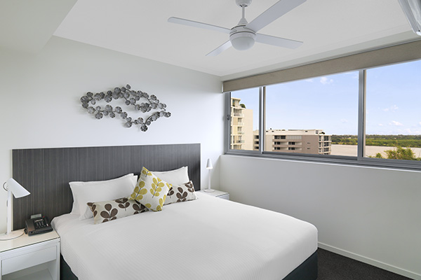 air conditioned bedroom with ceiling fan and Wi-Fi for guests staying in a two bedroom apartment at Oaks Rivermarque hotel in Mackay, Queensland, Australia