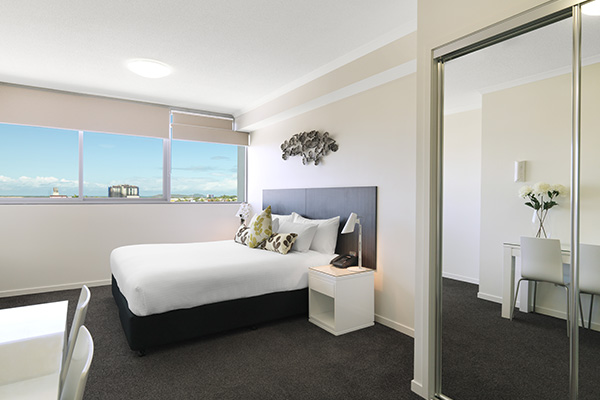 full length mirror in bedroom with queen size bed in hotel room apartment at Oaks Rivermarque in Mackay, Queensland, Australia