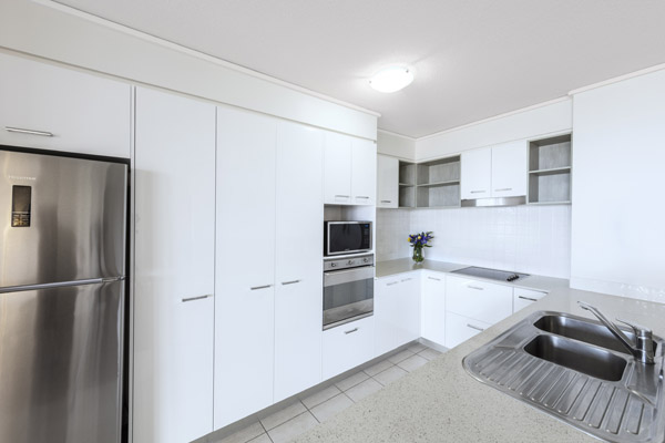 kitchen with microwave, fridge, oven and cupboards in one bedroom apartment at Oaks Seaforth Resort hotel, Sunshine Coast, Queensland, Australia