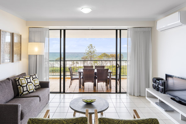 air conditioned living room with comfortable couches and private balcony outside with views of ocean and Sunshine Coast beach near Mooloolaba