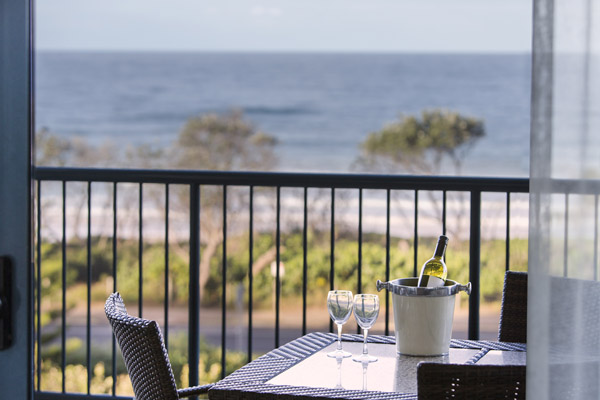 bottle of wine and glasses on table on balcony with view of beach and ocean in 2 bedroom apartment at Oaks Seaforth Resort hotel, Sunshine Coast