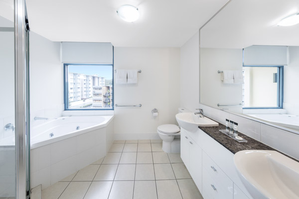 large en suite bathroom with spa bathtub, jacuzzi, large mirror, shower, toilet and clean towels at Oaks Seaforth Resort hotel, Sunshine Coast, Queensland