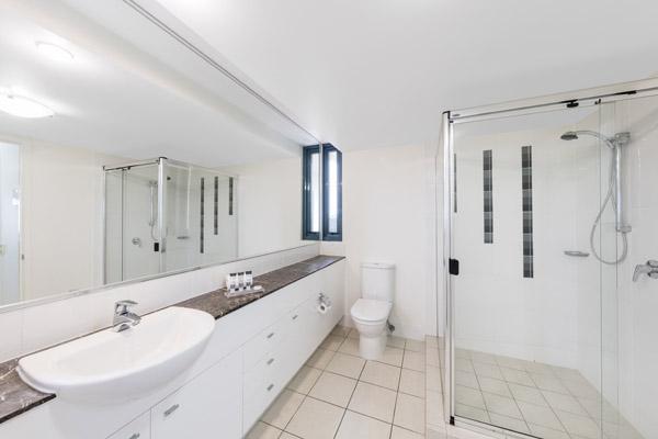large shower and toilet in en suite bathroom of family friendly 3 bedroom apartment at Oaks Seaforth Resort hotel, Alexandra Headlands, Sunshine Coast, Australia