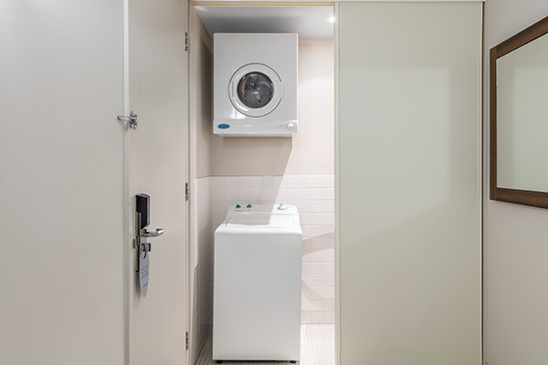 washing machine and dryer in laundry in 1 bedroom apartment at Oaks Embassy hotel Adelaide City, South Australia