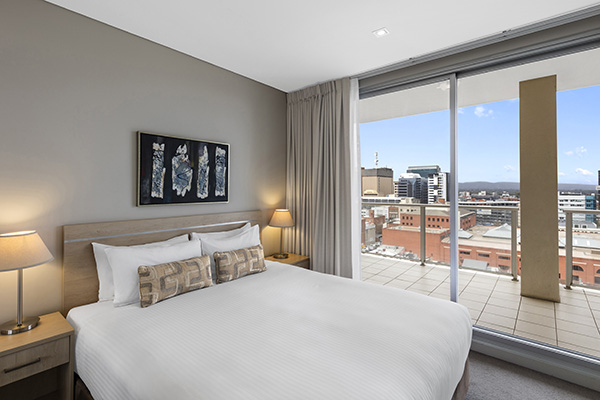 queen size bed in air conditioned room with Wi-Fi and balcony outside with table and chairs and views of Convention Centre in Adelaide
