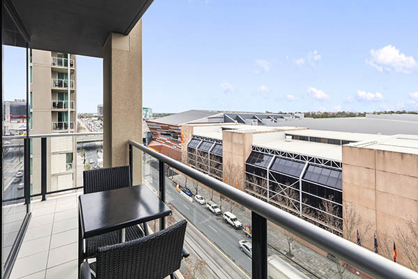 large balcony with black table and chairs with views of Adelaide city and blue sky in background