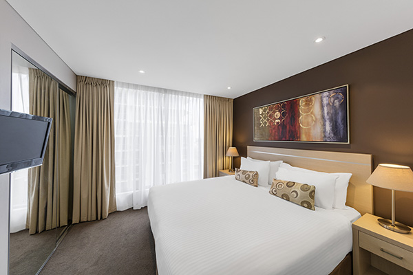 Hotels Adelaide CBD with sunlight pouring through curtains into 2 bedroom hotel apartment with queen size bed, satellite TV and pictures on walls