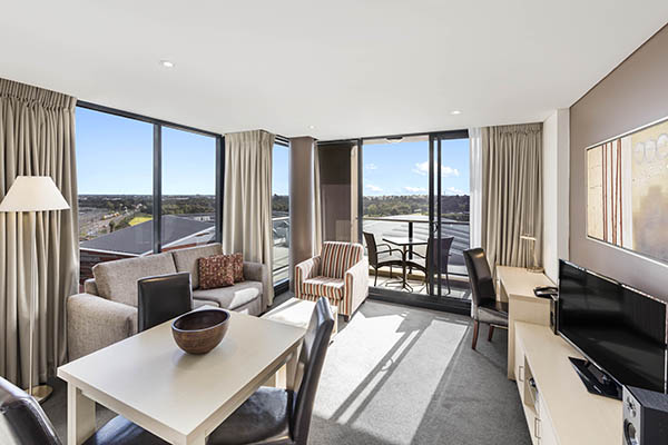 Hotels Adelaide CBD living room with lamp, table, TV, aircon and Foxtel, air conditioning and furnished private balcony with view of Adelaide Oval cricket ground