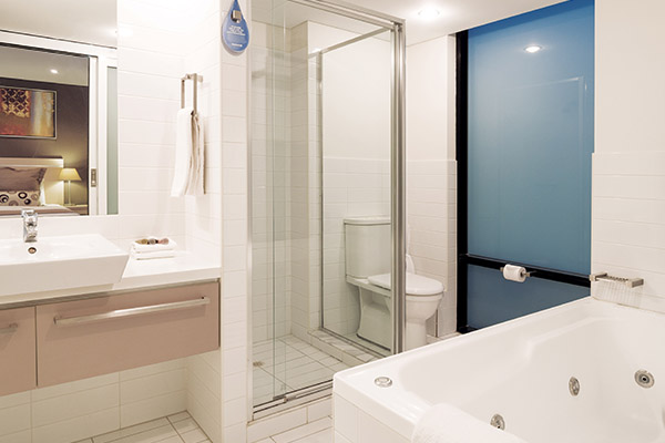 big spa bath in en suite bathroom with shower, toilet and large mirrors in 2 bedroom apartment near Adelaide Oval, perfect for sports lovers