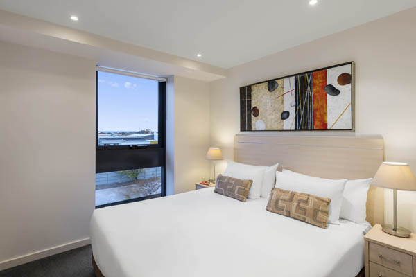 queen size bed in large, air conditioned master bedroom of 2 bed hotel apartment near Adelaide Convention Centre