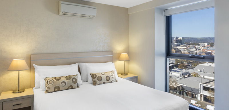 Adelaide hotels with large bed with air conditioning unit above in 2 bedroom apartment with free wi-fi near Adelaide Convention Centre