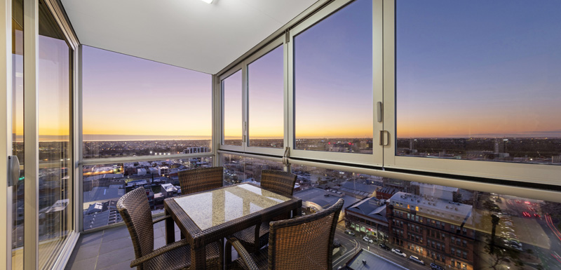 table and chairs on balcony with view of beautiful sunset in background at iStay Precinct hotel in Adelaide city, South Australia