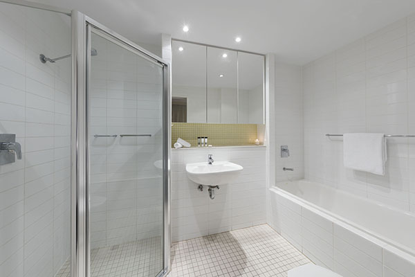 en suite bathroom with clean towels, disabled access shower and large mirror in 1 bedroom apartment at Oaks Liberty Towers hotel in Glenelg