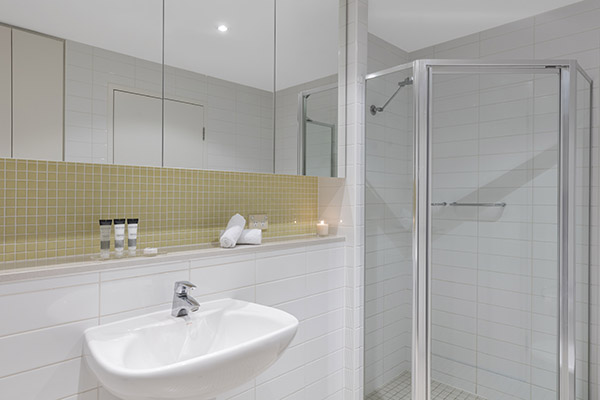 large shower, toilet and sink in en suite bathroom of 2 bedroom hotel apartment near Glenelg beach, South Australia