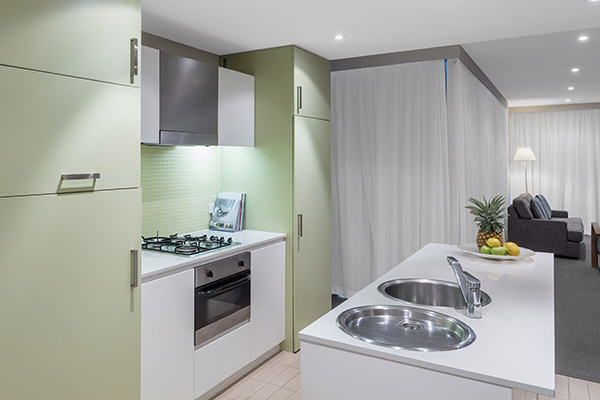 kitchen with stove, oven and counter top for preparing vegetarian meals at Oaks Liberty Towers hotel in Glenelg, South Australia
