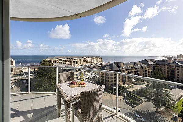 Glenelg hotels with huge balcony with vegan food on table and great views of ocean at family friendly 3 bedroom apartment at Oaks Liberty Towers hotel in Glenelg, South Australia