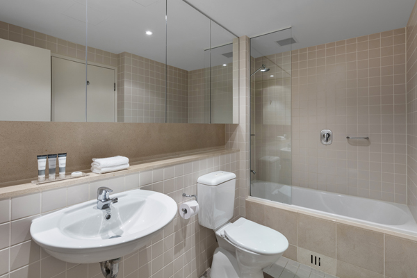 clean en suite bathroom with bath, shower, toilet and large mirror in 1 bedroom ocean view apartment near beach at Oaks Plaza Pier hotel in Glenelg, South Australia