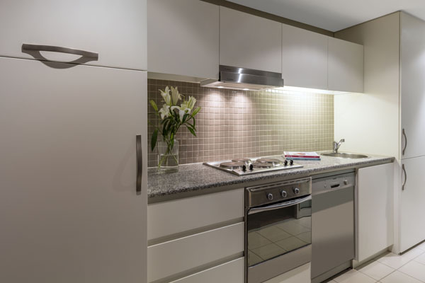 kitchen with fridge, freezer, oven, mircowave, kettle, tea pot, coffee mugs and toaster in air conditioned 2 Bedroom Apartment at Oaks Plaza Pier hotel in Glenelg, South Australia