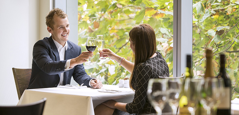 couple on romantic getaway to Melbourne city toasting glasses on table in 1st Floor Restaurant on Collins Street next to window