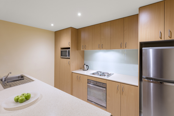 large kitchen with plenty of cupboards for storage, big fridge, freezer, oven, dishwasher and microwave in 1 bedroom hotel apartment at Oaks on Lonsdale, Melbourne CBD, Victoria, Australia
