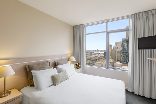 sun shining through large windows onto queen size bed in Melbourne hotel apartments 2 bedroom accommodation with Wi-Fi access and Foxtel at Oaks on Lonsdale hotel, Victoria, Australia