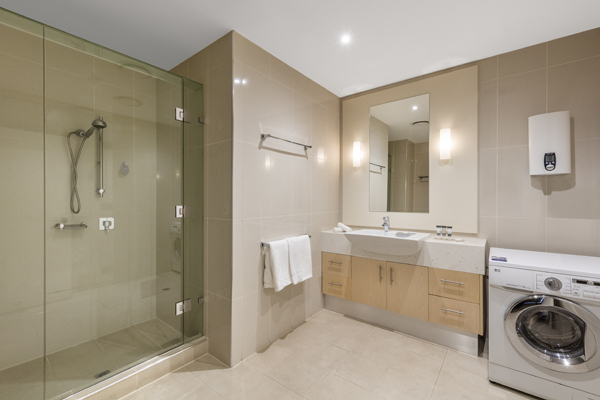 large en suite bathroom with washing machine, shower and clean towels in Hotel Apartment at Oaks On Lonsdale in Melbourne city, Victoria, Australia