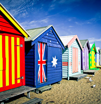 row of brightly coloured painted huts on Brighton Beach in Melbourne with blue sky in background