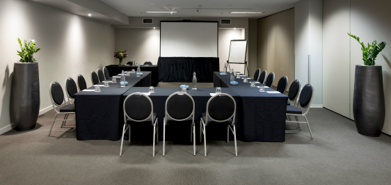 air conditioned room with large projector screen, tables and chairs in air conditioned conference room for hire in Melbourne city