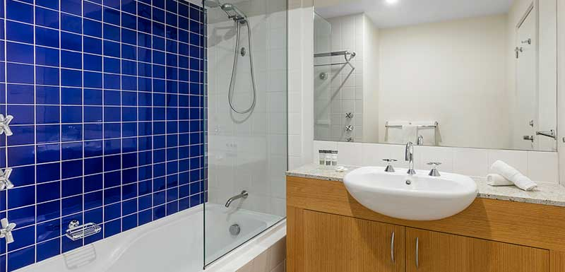 melbourne cbd hotels clean en suite bathroom with bath, shower, toilet and big mirror in Studio Apartment at Oaks on Market hotel in Melbourne city, Victoria, Australia