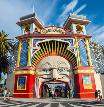 Family at Luna Park amusement park entry near St Kilda Beach in Melbourne during summer holidays