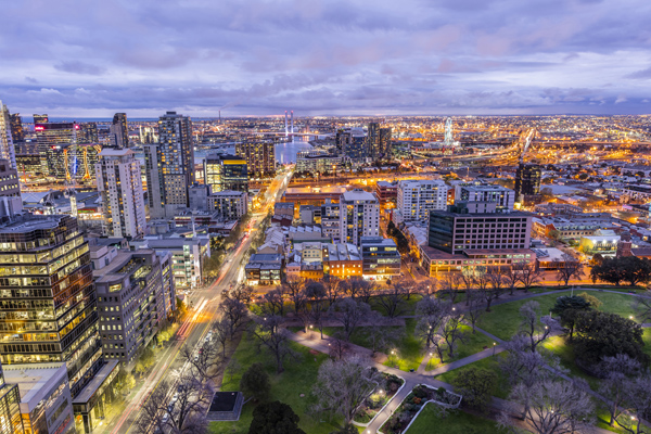 aerial view of Melbourne city at sunset with cars parking on street, public park and tall buildings, seen from private balcony of hotel Studio Apartment on William St