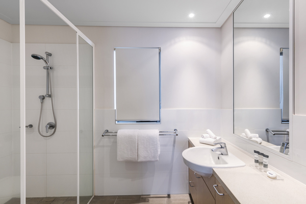 clean en suite bathroom of Oaks Broome hotel room with shower, toilet and fresh white towels in Western Australia