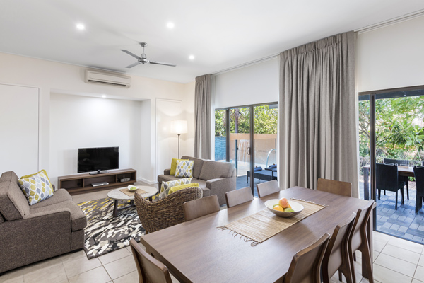 spacious air conditioned living room with sliding glass doors leading to large private balcony outside, Foxtel on television, ceiling fan and modern furniture in Broome, Western Australia