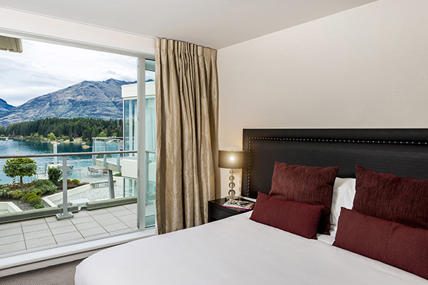 comfortable double bed in large 1 Bedroom Apartment with free Wi-Fi access and private balcony at Oaks Club Resort hotel in Queenstown, New Zealand