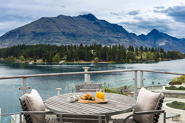 delicious hotel breakfast menu option with orange juice on table on private balcony at Oaks Club Resort hotel in Queenstown with The Remarkables mountain range and Lake Wakatipu in background
