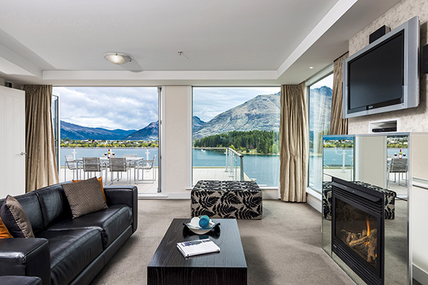 Queenstown ski resorts with Wi-Fi spacious living room, fireplace, Sky TV, leather couches, and large private balcony with views of Lake Wakatipu and The Remarkables mountain range in New Zealand