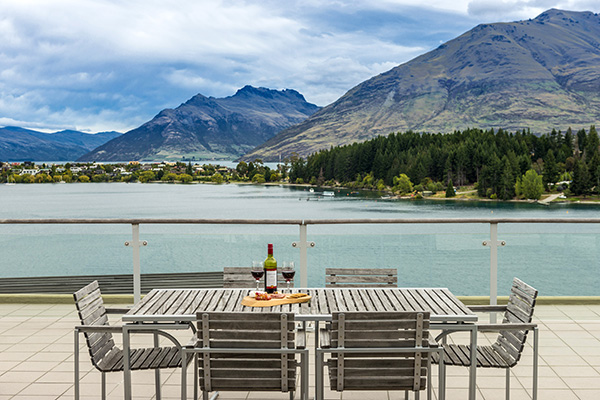 bottle of wine, champagne glasses and delicious vegetarian food on table on private balcony of 3 Bedroom hotel apartment in Queenstown overlooking Lake Waktipu